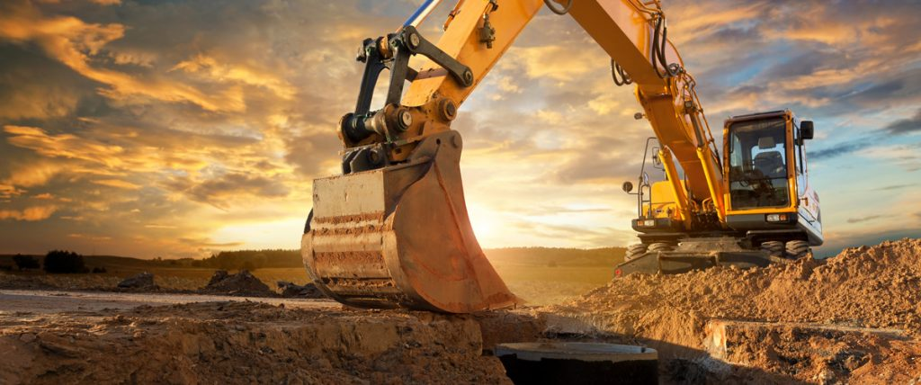 excavator on soil with a sunset in the background